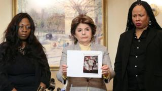 Rochelle Washington (l), lawyer Gloria Allred and Latresa Scaff display photos taken on the night of the alleged abuse by R Kelly at Lotte New York Palace on February 21, 2019