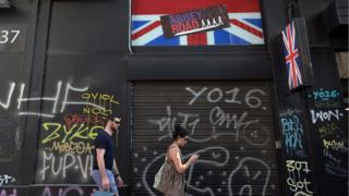 A picture of a man and woman waling past a shop front with a union jack sign above it