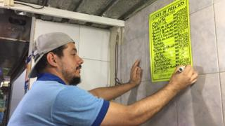 Un empleado remarca la lista de precios.