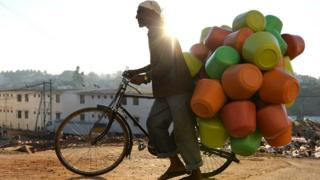 This photo taken on March 18, 2015 shows a vendor carrying colourful plastic water pots on his bicycle to sell to households in Bangalore.