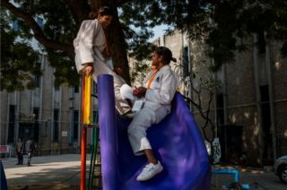 Two women talk on a slide