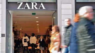 Shoppers walking past the entrance to a Zara store.
