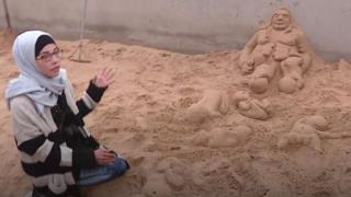 فلسطينية تنحت على الرمال هموم شعبها