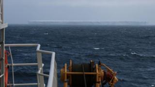 Large rectangular iceberg spotted in the middle of the ocean. The sky is grey.