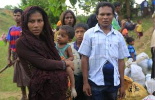 Rasida, who is nine months pregnant, waits with her family as they look for a space to set up their makeshift home