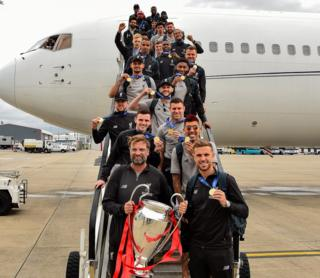 Jurgen Klopp and players with trophy as they come out of plane