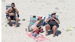 آقای کریستی گفت آفتاب نگرفته ولی تصاویر هوایی او و خانواده اش را در حال آفتاب گرفتن در ساحل خالی نشان می دهد