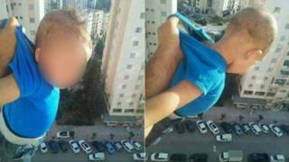 أب يدلي طفله من النافذة