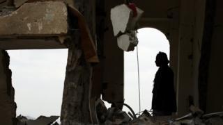 يمني يجلس وسط أنقاض منزل