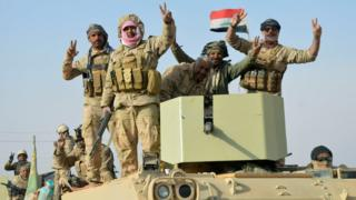 Iraqi forces make victory signs after capturing the town of Rawa on 17 November 2017