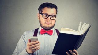 Hombre leyendo libro y usando celular
