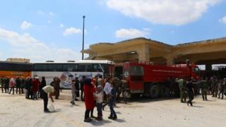 "People, who were evacuated from the two rebel-besieged Shi""ite villages of al-Foua and Kefraya, stand near buses at insurgent-held al-Rashideen"