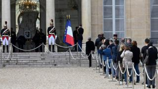 French public queue to pay tribute in front of a picture of the late French President Jacques Chirac displayed at the Elysee presidential palace