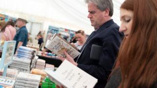 Seorang pria dan seorang wanita membaca buku di toko buku.