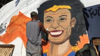 Grafiteiro pinta mural com o rosto sorridente de Marielle