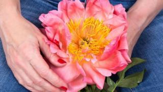 Mulher segura flor