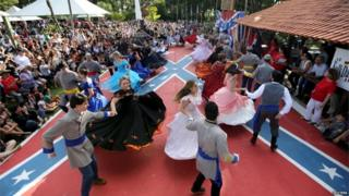 """Descendants of American Southerners wearing Confederate-era dresses and uniforms dance during a party to celebrate the 150th anniversary of the end of the American Civil War in Santa Barbara D""""Oeste, Brazil, April 26, 2015."""