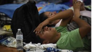 A man lies on a hard floor in a temporary shelter in Escuintla department, 35 km south of Guatemala City on June 3, 2018