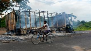 A biker passes by a burned truck on the side of the road in a village near Beoumi on May 17, 2019 after violence erupted between members of the Baoule local community and northern ethnic group Dioula people. Fighting erupted between people of the Baoule and Dioula tribes Wednesday at Beoumi, a town in the centre of the country, after an altercation between a taxi driver and a motorbike taxi operator at a taxi rank, said witness Innocent Koffi, a local farmer. The clashes caused nine deads and 84 injured people including six gendarmes and several houses and vehicles were set ablaze.