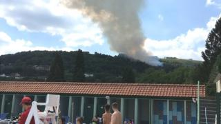 Fire in the hills above an outdoor swimming pool