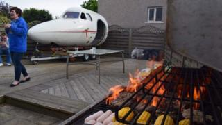 A plane cockpit in a back garden - in the foreground there is a barbeque with sausages on it