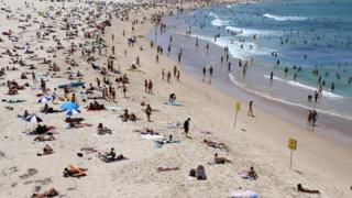 People enjoy a beach in Sydney