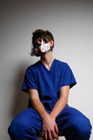 A junior doctor with face mask on at home