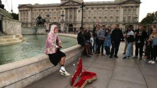 Justin Bieber busks while sitting on the edge of a fountain outside Buckingham Palace, while fans watch on