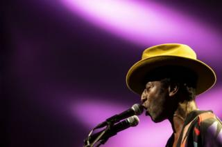 Keziah Jones sings into a microphone. His eyes are closed and he wears a yellow, wide-brimmed hat tipped forward. The background is a vivid purple.
