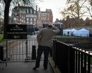 A man next to a sign and gate at College Green