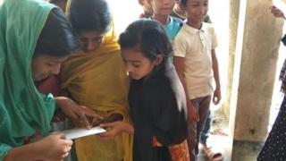 বাংলাদেশের একটি গ্রামে পরীক্ষার ফল দেখছেন শিশু শিক্ষার্থীরা।