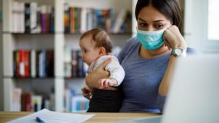 Woman with baby looks at computer