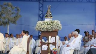 Imagem mostra missa na Esplanada dos Ministérios em comemoração à padroeira do Brasil, Nossa Senhora Aparecida, em 2016. Imagem da santa aparece em primeiro plano