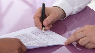 Person signing a contract for employment