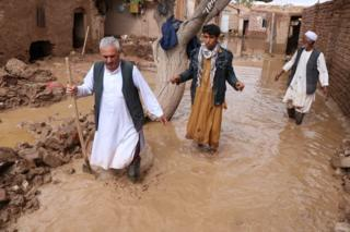 Afghanistan - people wade through flood water in Herat