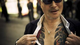 A man showing off tattoos