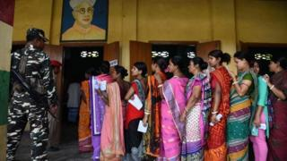 """Indian voters stand in queue to cast their votes at a polling station as security personnel stand guard during India""""s general election in Amoni village, some 150 kms from Guwahati, the capital city of India""""s northeastern state of Assam on April 11, 2019."""