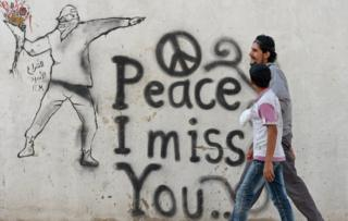 Syrian youths walk past graffiti in the rebel-held Syrian city of Minbej 10 October 2012
