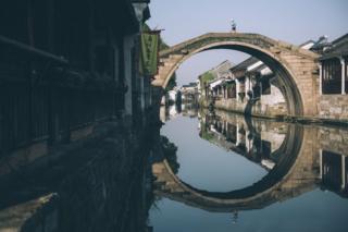 Mina Guli crosses a bridge over a water canal in Nanxun, China
