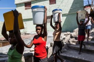 Young girls carry water from the main water-filling station back to their respective homes