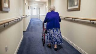 old lady walks down corridor in care home