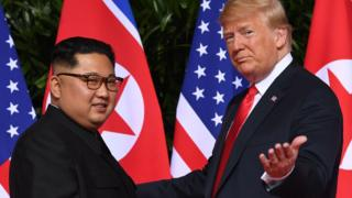 US President Donald Trump (R) meets with North Korea's leader Kim Jong Un (L) at the start of their US-North Korea summit, at the Capella Hotel on Sentosa Island in Singapore, 12 June 2018