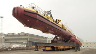 A tidal generator on its side waiting to be launched.