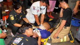 Rescue workers aid a victim after an accident, possibly caused by a fire retardant chemical according to the bank, at the headquarters of Thailand's Siam Commercial Bank in Bangkok 13 March 2016