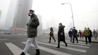 People in face masks walk through a smoggy Beijing street
