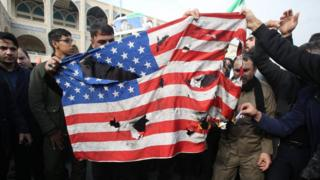 Iranians in Tehran demonstrate against Gen Soleimani's killing and burn US flag