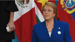 Bachelet detrás de unas banderas