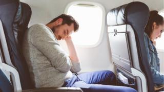 Un hombre duerme en un avión