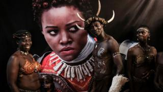 Dancers stand in front of pster for di Africa premiere of Black Panther film for Kisumu, Western Kenya