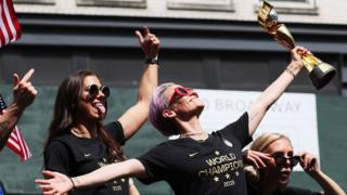 Alex Morgan and Megan Rapinoe celebrate at a parade for the World Cup winning team